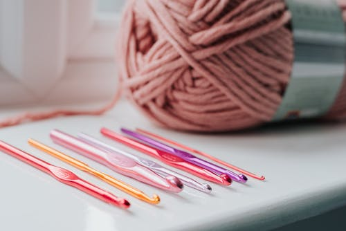 Closeup of row of multicolored crochet needles and ball of beige threads for knitting in bright room