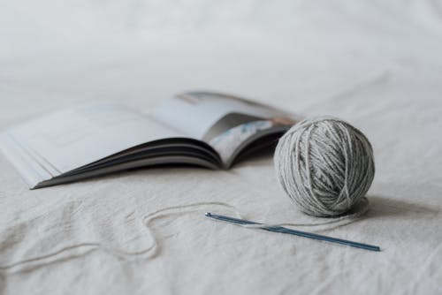 Small spherical gray ball of threads and crochet needle with opened magazine on white fabric in bright room