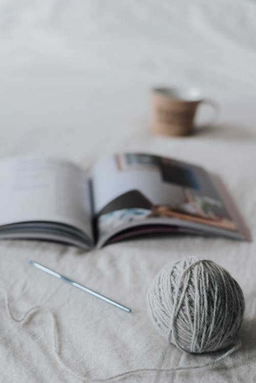 Composition of gray yarn ball and crochet needle placed on comfy bed with opened magazine and cup of hot drink