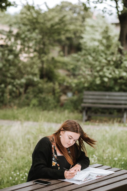 Focused woman writing in notebook in park