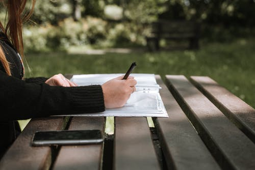 Anonymous female in casual clothing writing in copybook on wooden bench in sunlight on blurred background