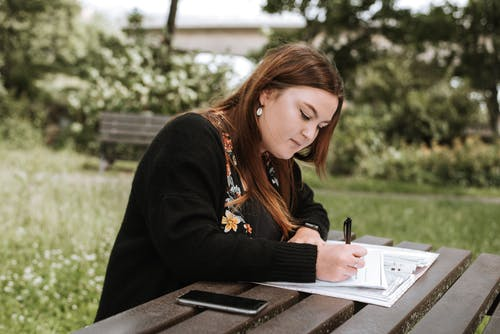 Concentrated woman writing notes in papers in park
