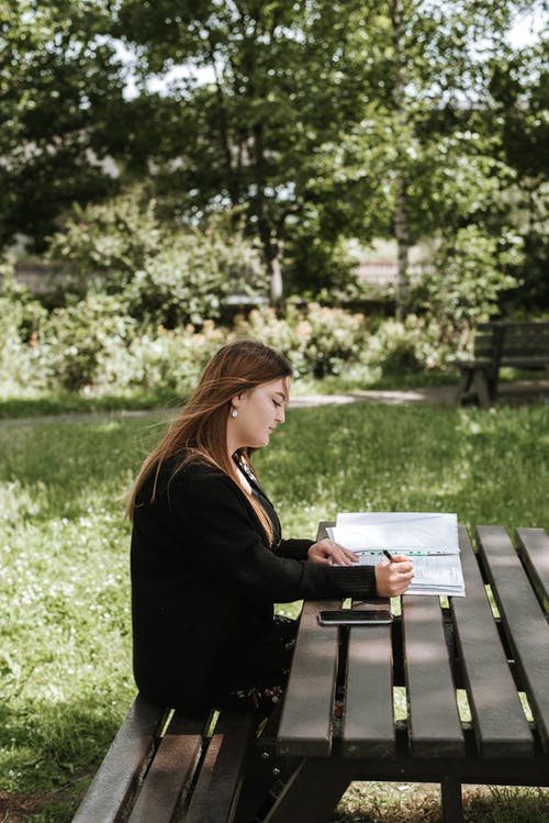 Woman reading and writing notes in diary
