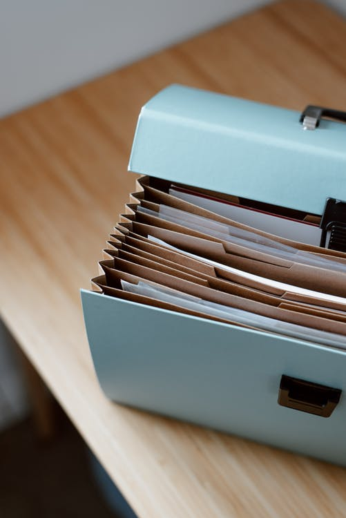 From above of opened modern briefcase with prepared papers placed on timber table in soft focus