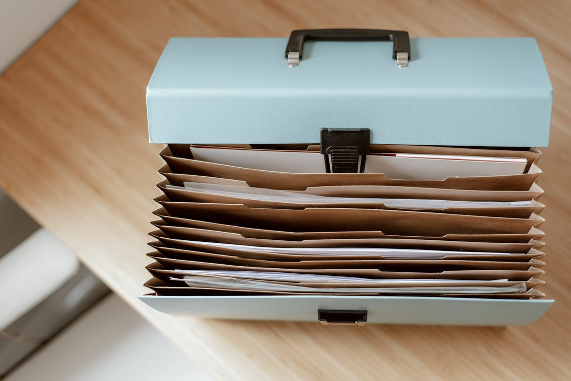 From above of briefcase for documents with papers placed on wooden table in daytime