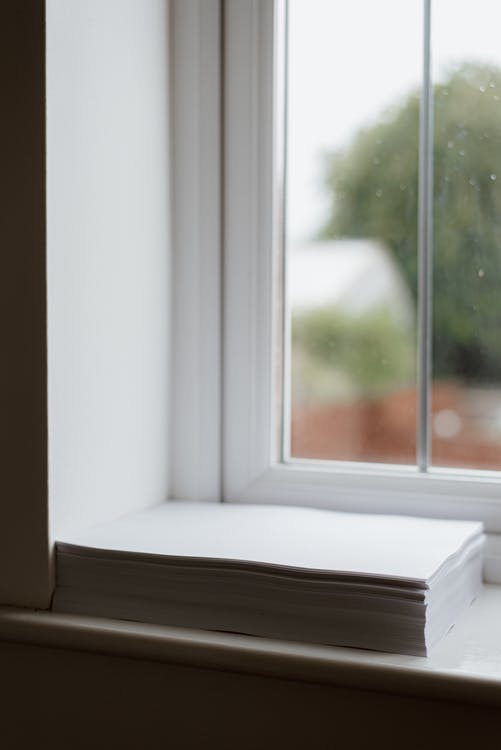 Stack Of White Paper Placed On Windowsill