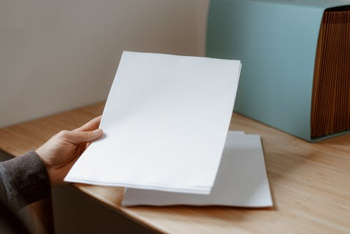 Crop anonymous person demonstrating empty sheet of paper against wooden table with folder for documents