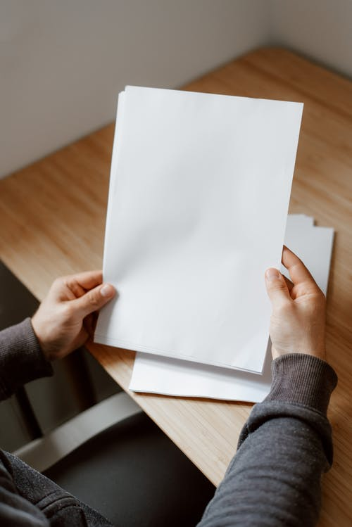 High angle of person sitting at empty wooden table and showing sheet of paper