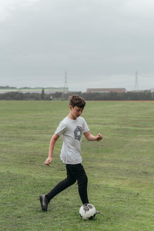 Boy playing football in green field