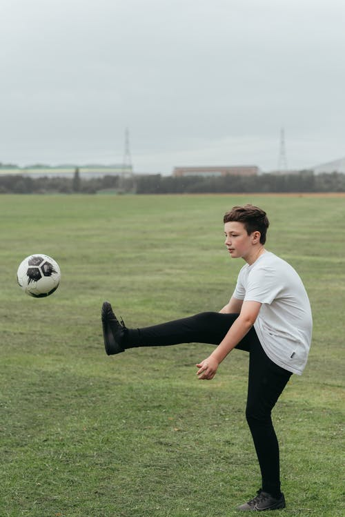 Side view of boy kicking ball while playing football in field in daytime