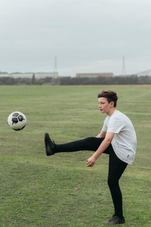 Boy kicking football ball in field