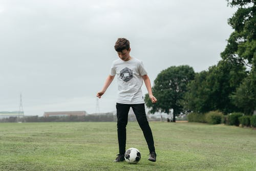 Concentrated boy playing football in field