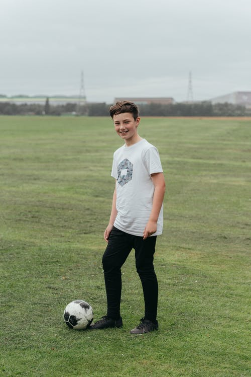 Smiling boy in casual clothes standing near football ball in field with green grass