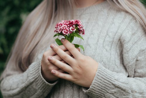 Peaceful female standing with pink flowers in hands