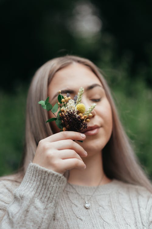 Reflective woman covering eye with dry bouquet in park