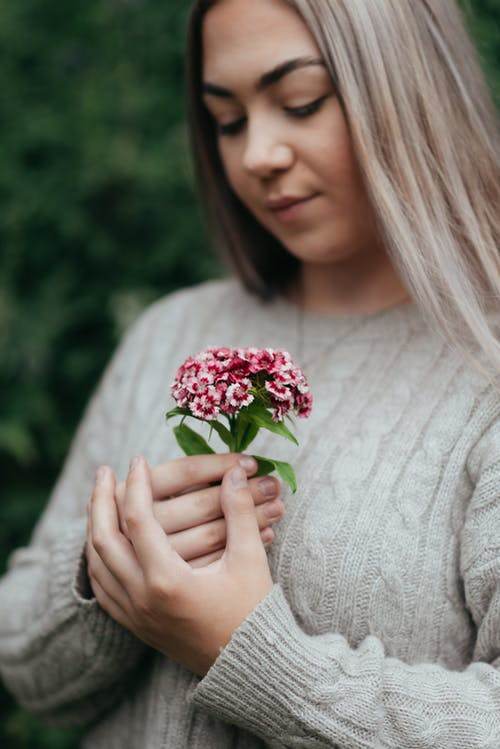 Crop young gentle female in knitted sweater with ornament and bright blossoming flowers looking down on blurred background