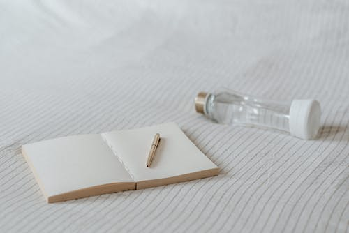 在床上的裝飾瓶附近的空記事本
