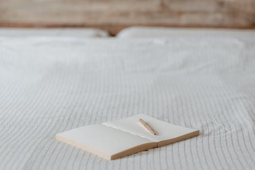 家のしわくちゃのベッドにペンで空の議題