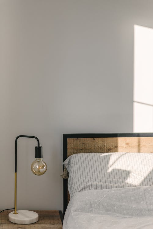 Bedroom interior with lamp near wall in sunlight