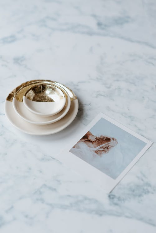 From above of collection of saucers with shiny ornament near photography of bride on marble table
