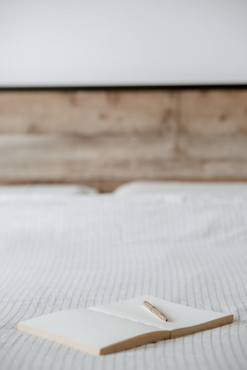 Agenda Kosong Dengan Pena Di Tempat Tidur Kusut