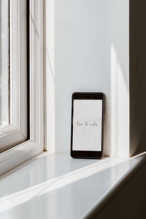 Smartphone Mit Aufschrift Auf Dem Bildschirm Auf Glänzendem Fensterbrett