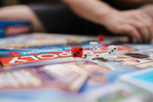 Unrecognizable player playing Monopoly at table with dices