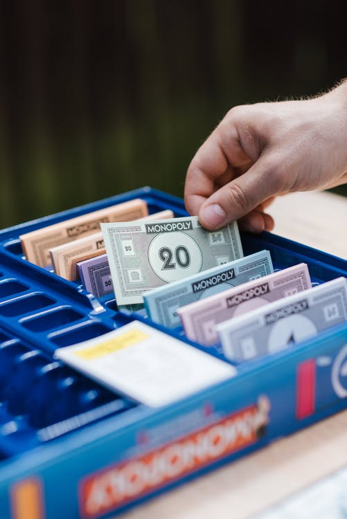 Crop unrecognizable person showing game banknote from collection in box while playing Monopoly at table