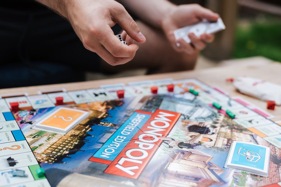 Crop anonymous male player with dices and fake money playing Monopoly at table with deed cards