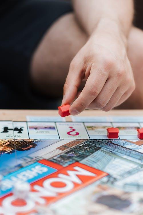 Hombre De Cultivo Jugando Monopolio Con Casas De Plástico En La Mesa