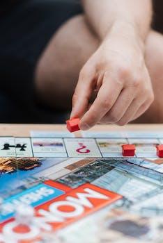crop man jouant au monopole avec des maisons en plastique a table