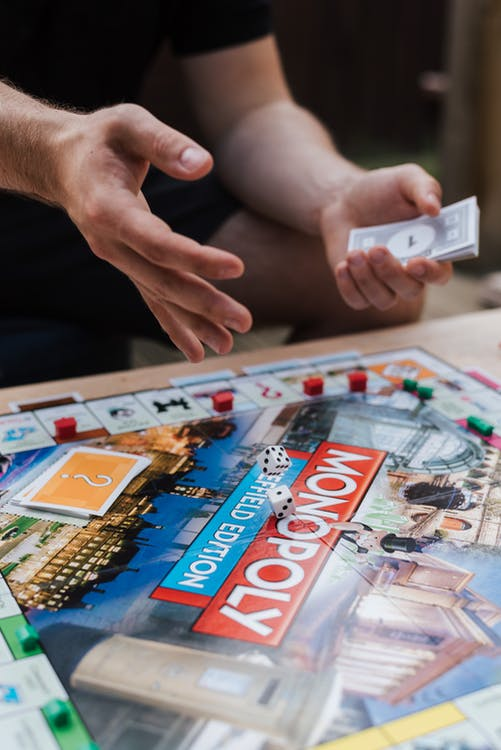 Crop unrecognizable man with fake cash playing board game while rolling dices at table with cards and plastic houses