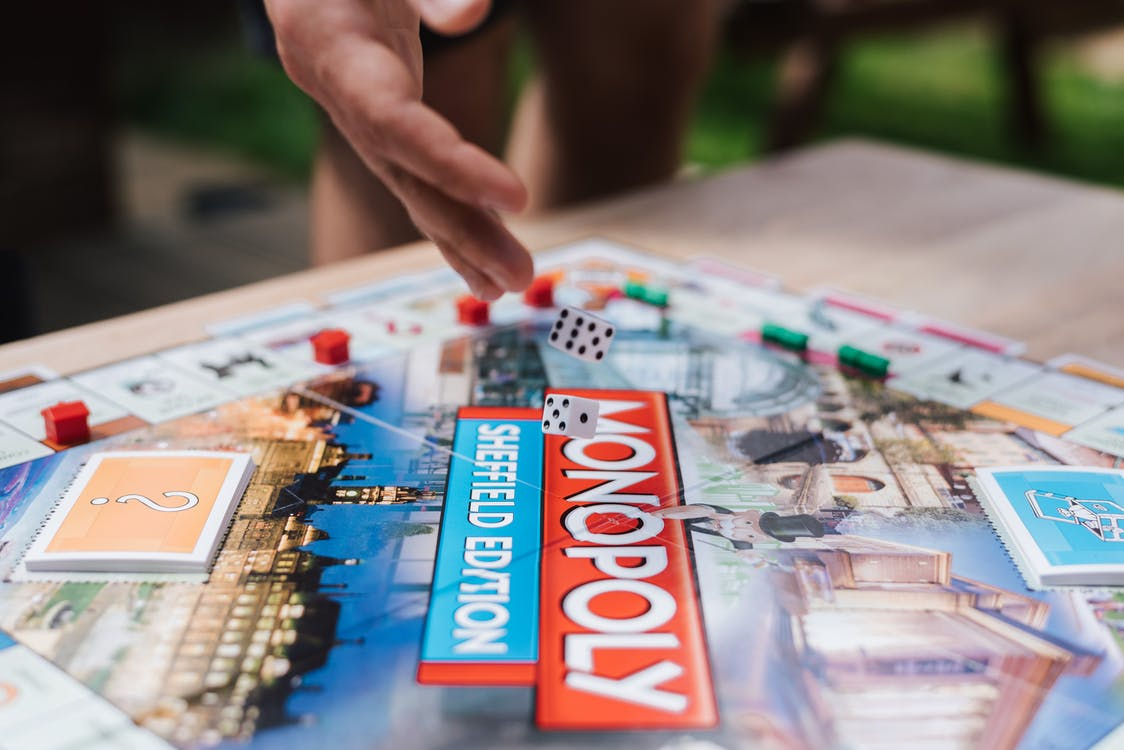 Close Up Photo of Rolling of Dice on Monopoly Board Game