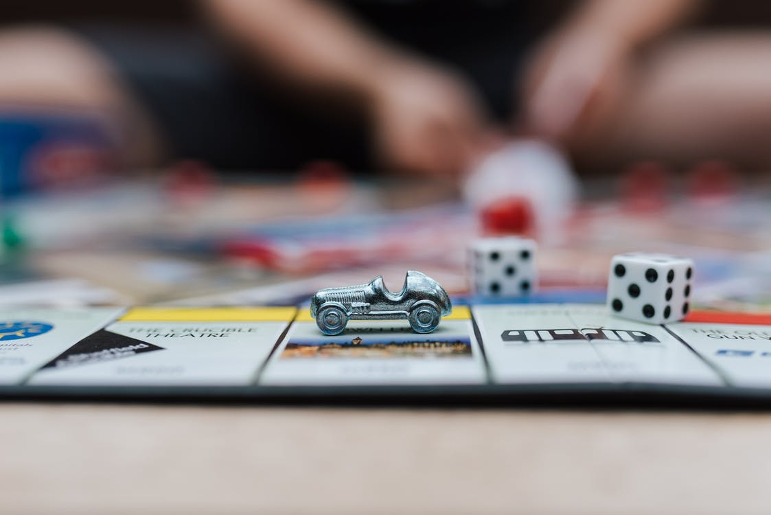 Crop anonymous man playing Monopoly at table with small plastic auto and similar dices