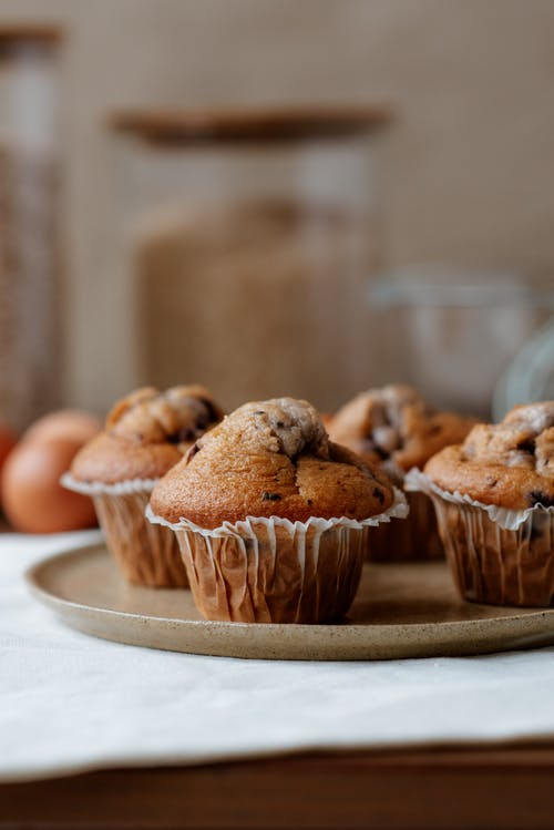 Tasty muffins with chocolate chips on plate