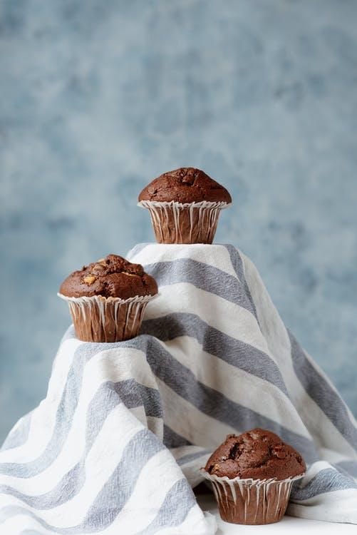 Composition of baked brown sweet muffins in forms placed on striped fabric in studio