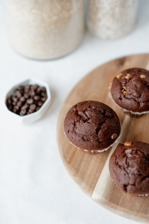 Sweet homemade chocolate muffins served on wooden tray