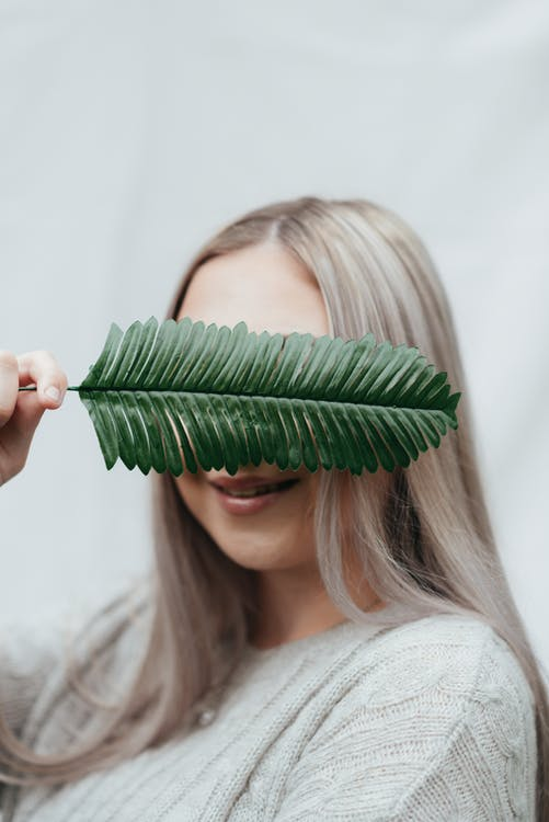 Smiling female covering face with green twig