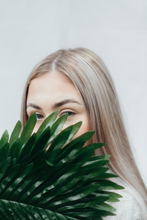 Young female covering half face with green branch of fresh exotic plant against white background