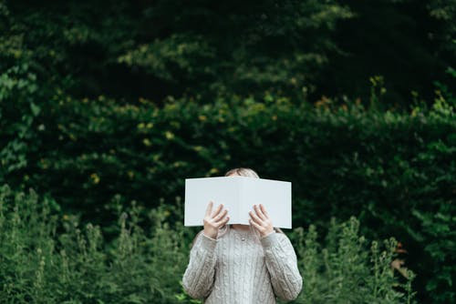 Woman covering face while reading book in nature