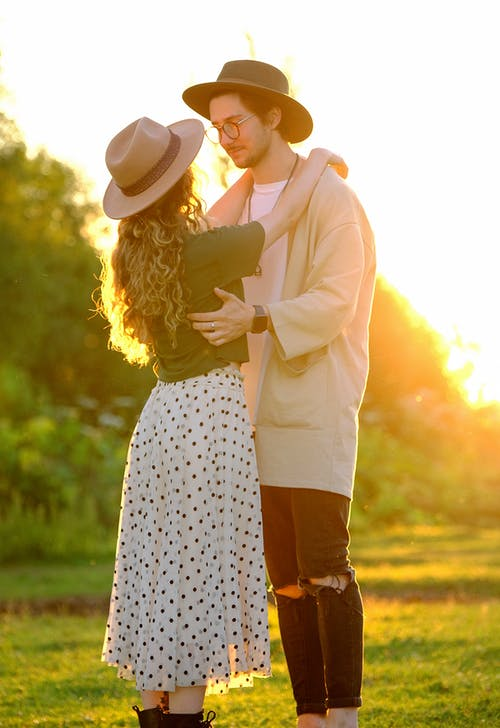 Young stylish loving couple embracing in countryside