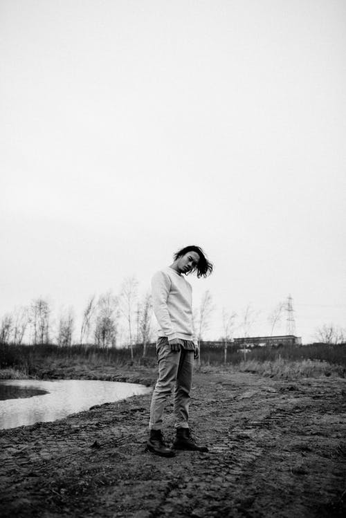 Confident man standing on dirty ground near pond