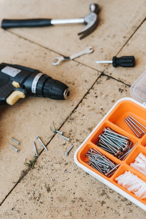 From above of assorted carpentry tools in plastic case placed with metal hammer and screwdriver