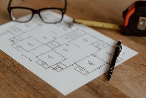 Pen with ruler and eyeglasses placed on house plan