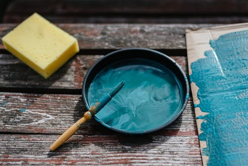 From above of turquoise paint in bowl with brush placed on wooden board near cardboard and sponge during repair work