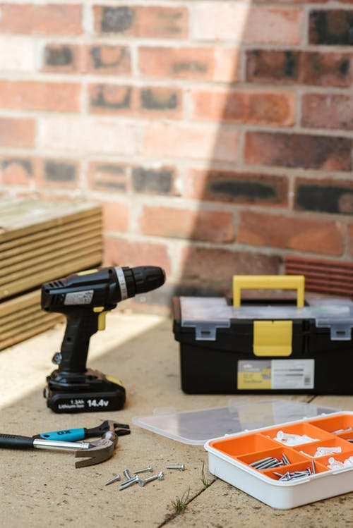 Cordless electric screwdriver placed on floor near boxes with various instruments and hammers against brick wall in sunlight on street