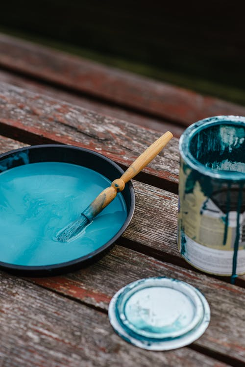 Bowl of paint near jar on bench