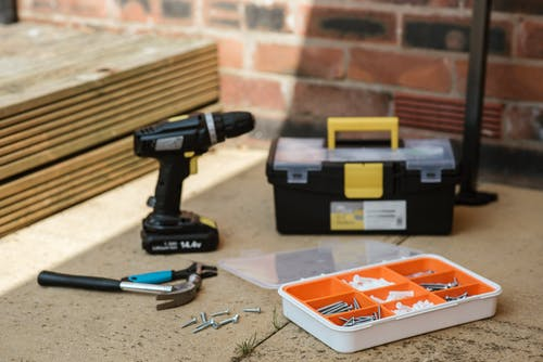 Electric screwdriver on floor near containers with instruments placed near spanner with hammer against brick wall  and wooden barrier
