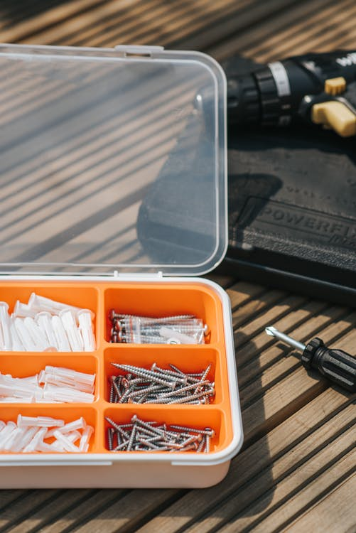 From above of various metal nails placed on wooden table near screwdriver in soft daylight