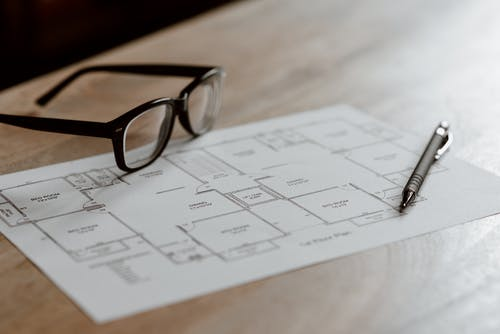 From above of eyeglasses near pen on plan placed on wooden table in apartment in soft daylight